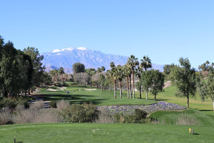 indian well golf course snow capped mountains and palm trees
