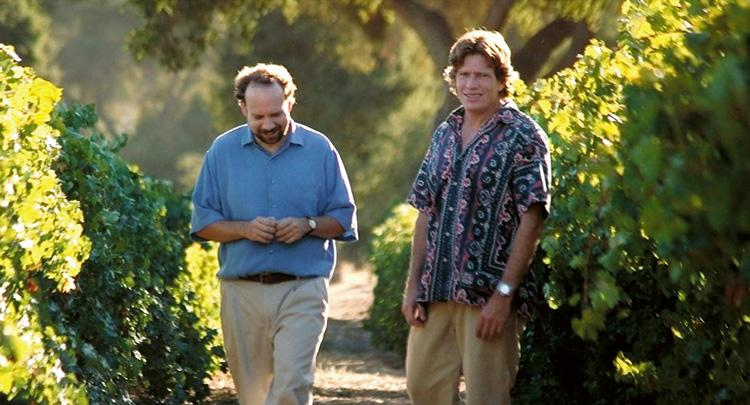 miles and jack walking through a vinyard