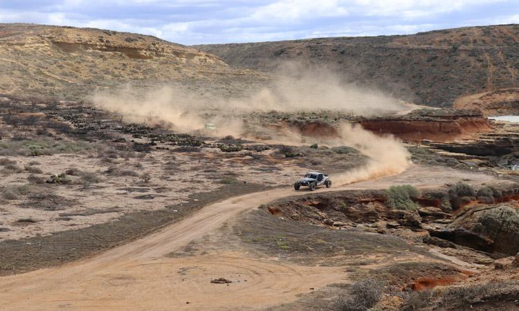 baja cars on dusty coastal road wide open baja